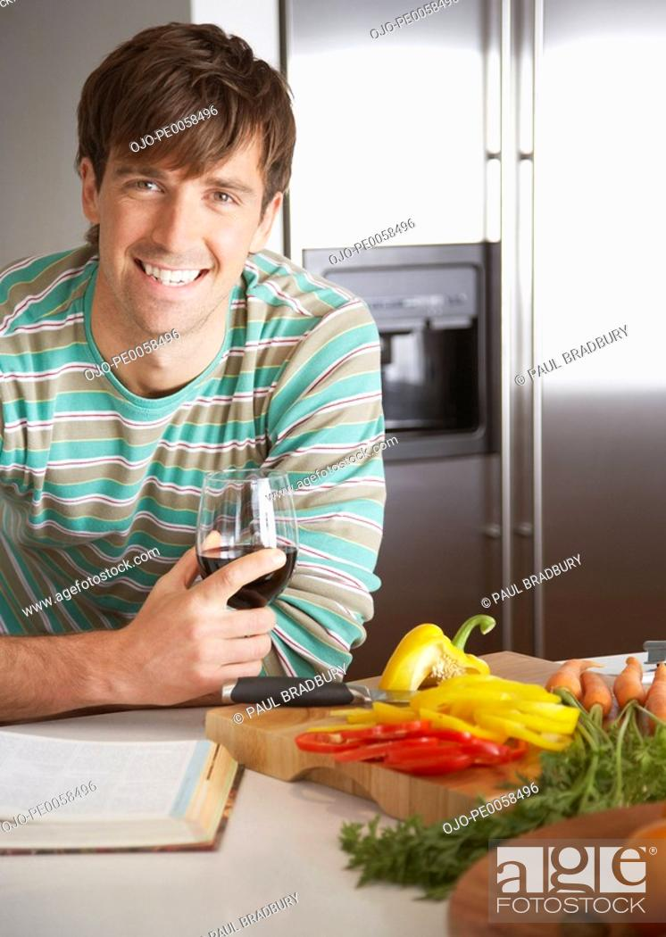 Stock Photo: Man with a glass of wine and chopped peppers beside him.