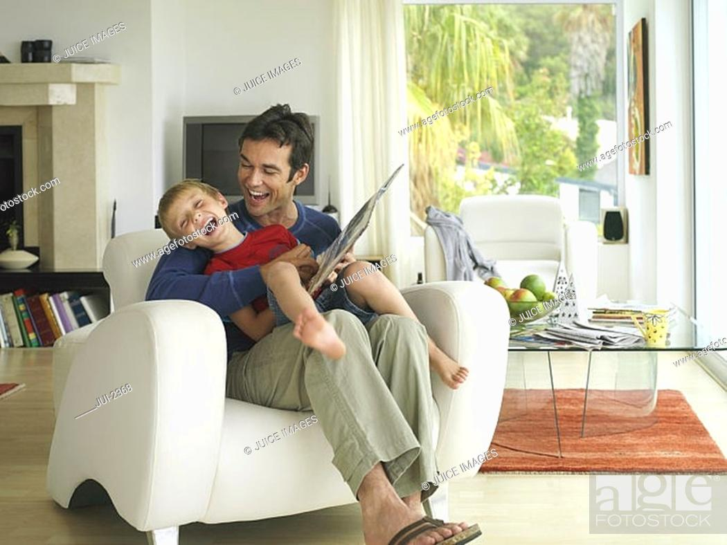 Stock Photo: Father and son 5-7 looking at photo album at home, boy in father's lap in armchair, laughing.