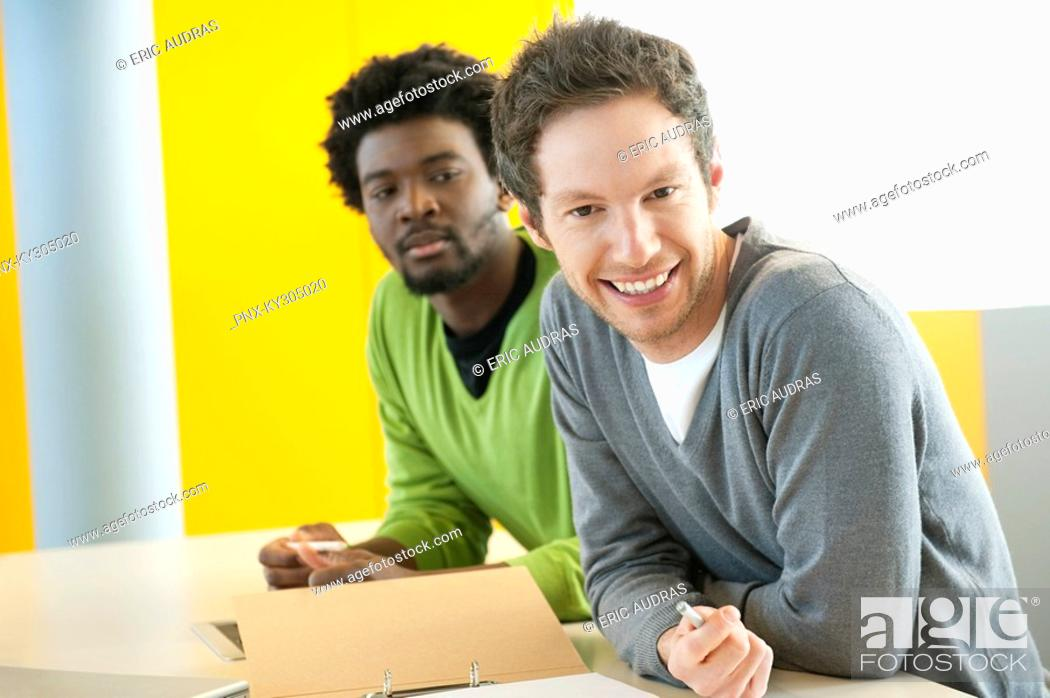 Stock Photo: Businessmen smiling in an office.