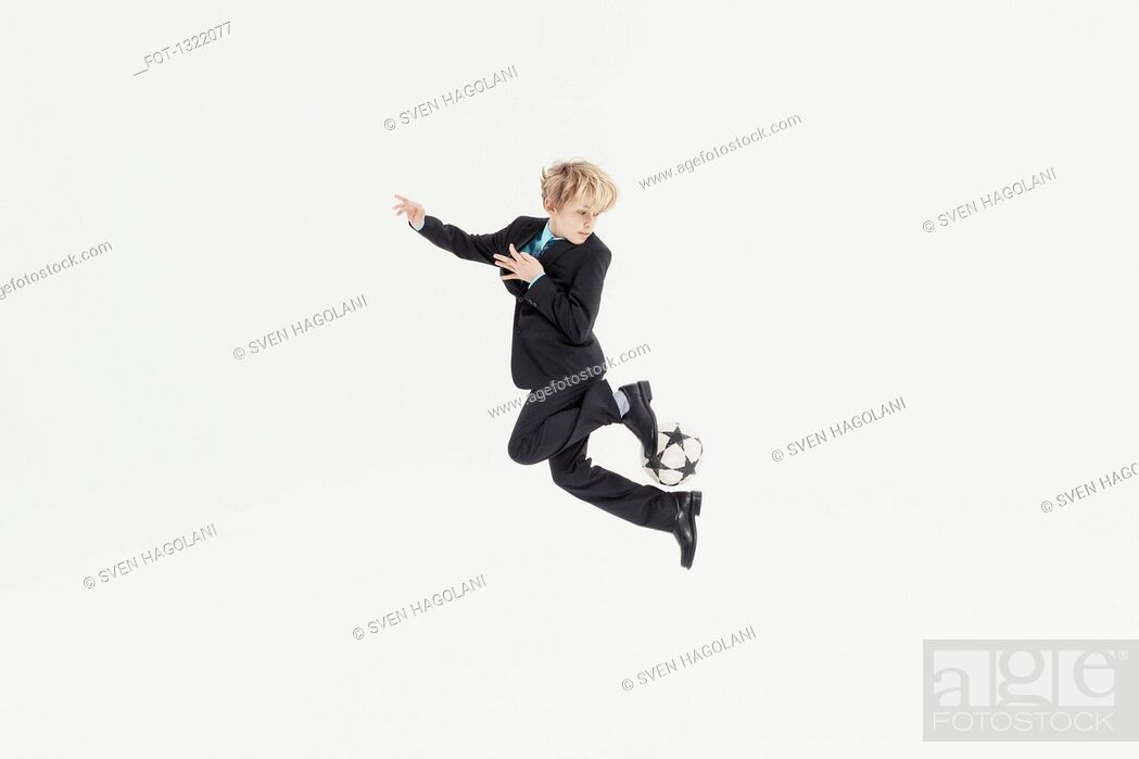 Stock Photo: Full length of boy dressed as businessman playing soccer against white background.