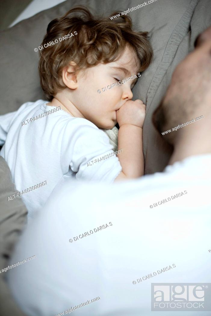 Stock Photo: Toddler boy sleeping beside father, cropped.