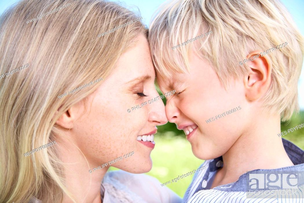 Stock Photo: Germany, Cologne, Mother and son touching forehead, close up.