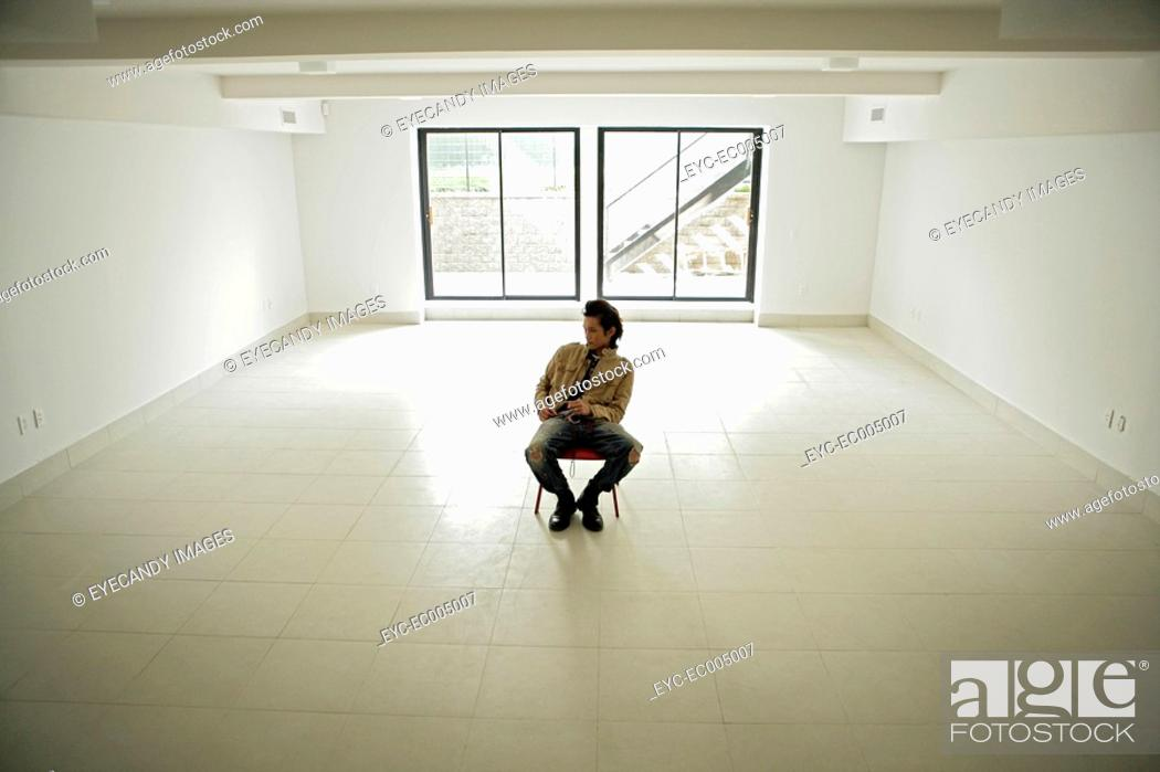 Stock Photo: One young man sitting inside room, high angle view.
