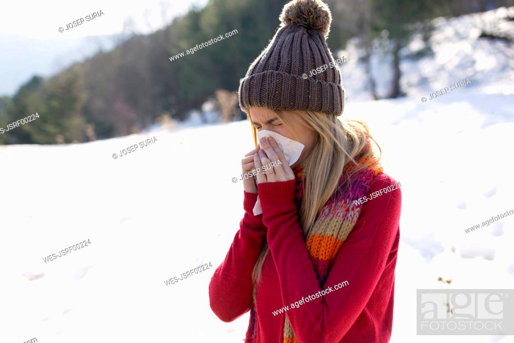 Stock Photo: Young blond woman blowing nose in winter.