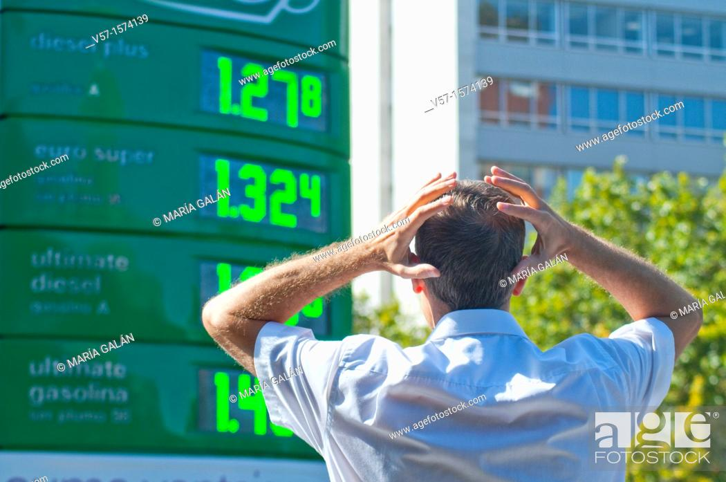 Stock Photo: Man looking astonished at petrol prices.