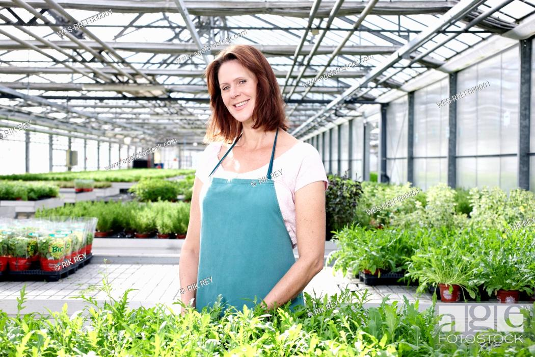 Stock Photo: Germany, Bavaria, Munich, Mature woman in greenhouse with rocket plants.