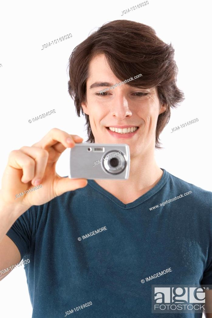 Stock Photo: Young man taking pictures with digital camera, smiling.