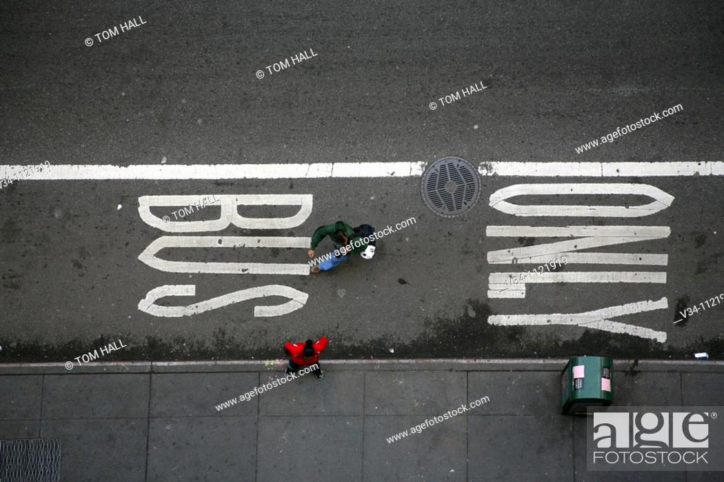 Stock Photo: Pedestrians walk past a BUS ONLY street sign in Manhattan.