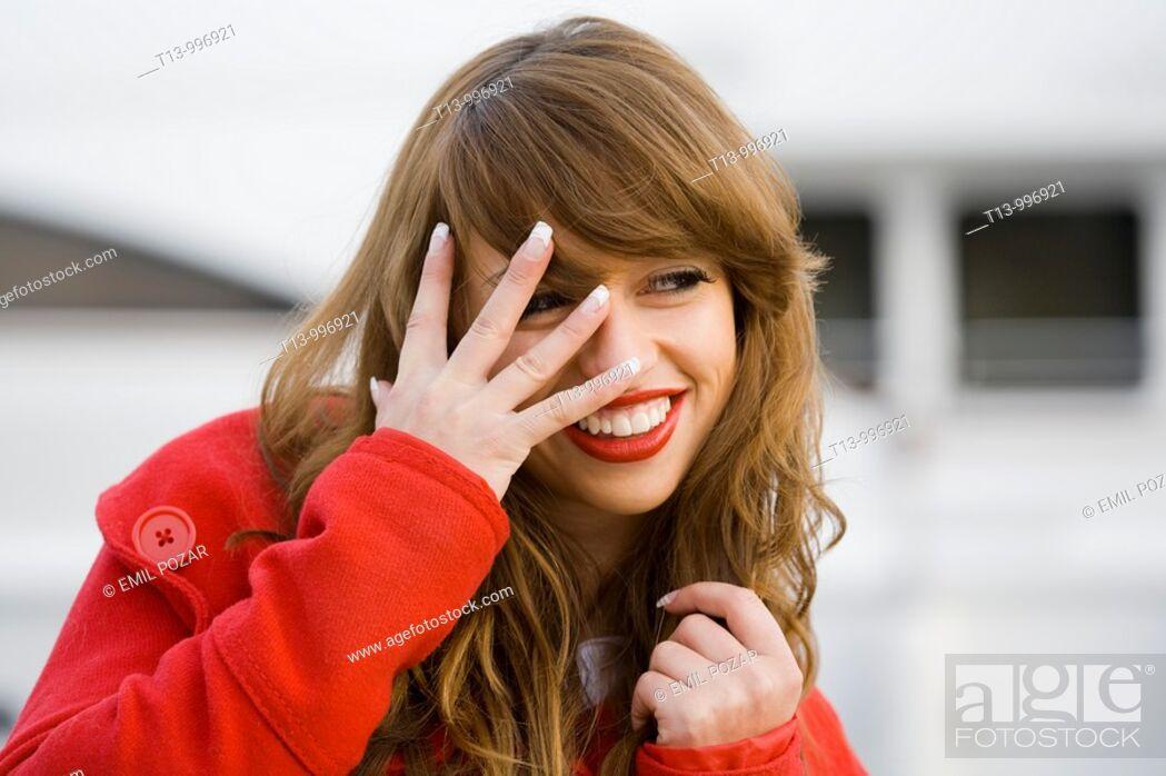 Stock Photo: Peeking and smiling through fingers pretty woman portrait.