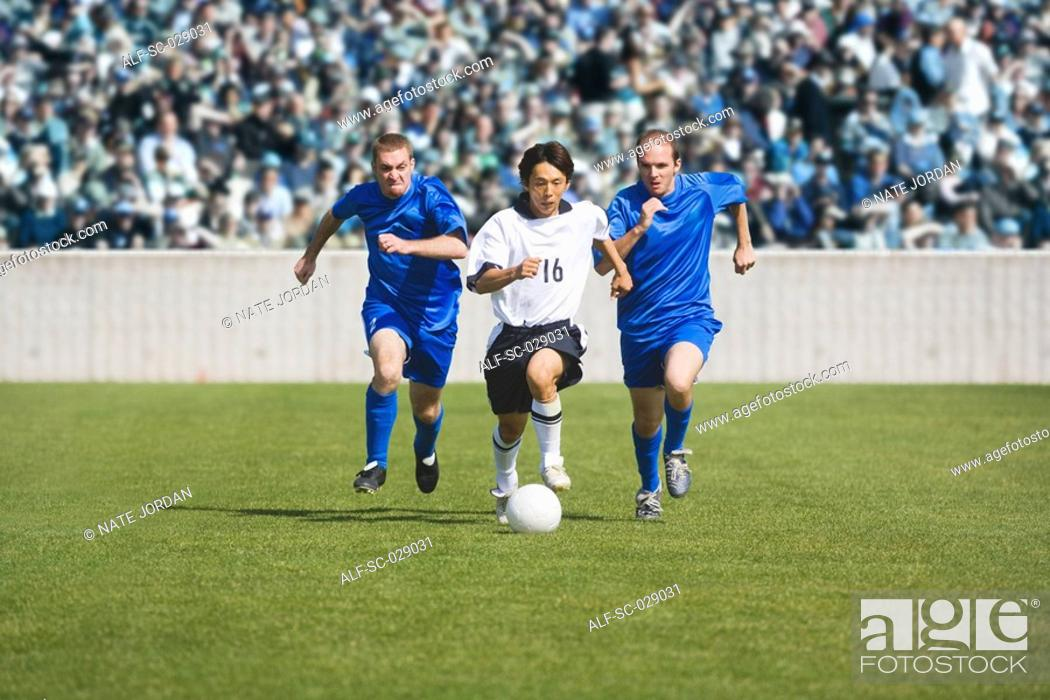 Stock Photo: Soccer Player Dribbling Past Defenders.