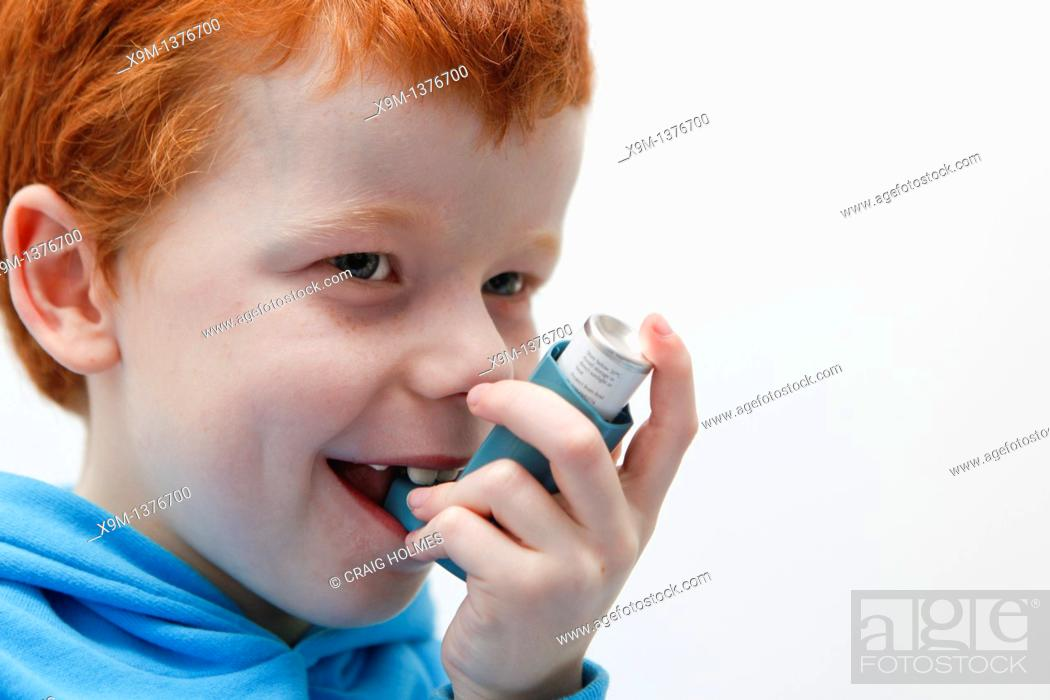 Stock Photo: Little boy using his asthma inhaler to alleviate symptoms.