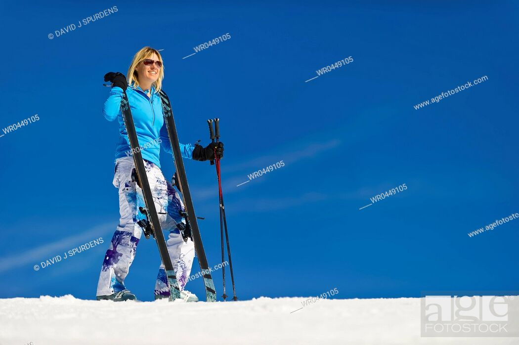 Stock Photo: A woman stands on the ski slope with her skis.