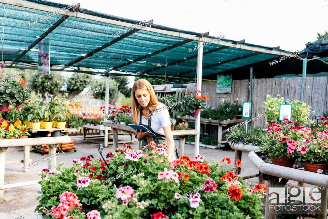 Imagen: Female worker in a garden center with a tablet caring for flowers.