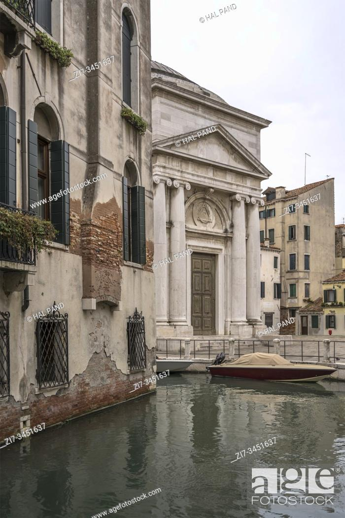 """Stock Photo: cityscape with Classical """"""""La Maddalena"""""""" church facade and canal nearby, shot in bright cloudy fall light at Venice, Veneto, Italy."""