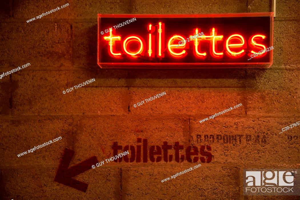 Stock Photo: Arty original toilettes restrooms indication in red neon light.