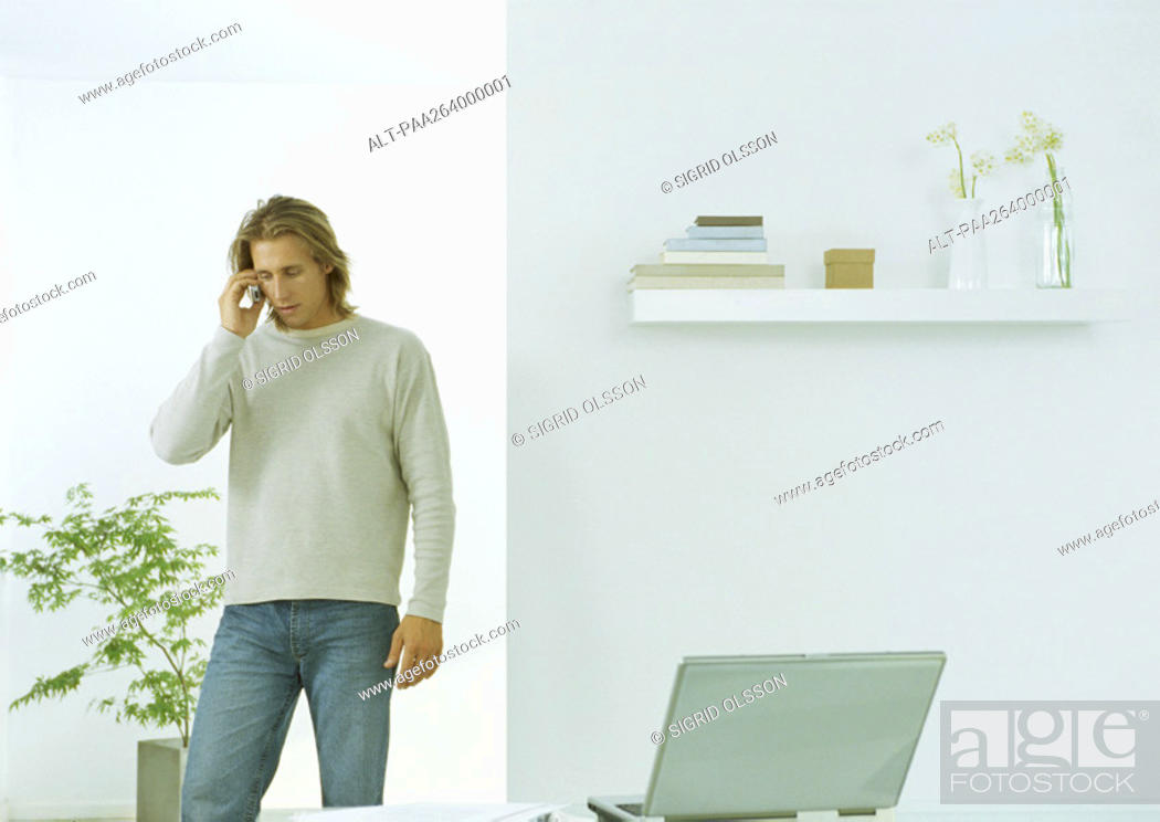 Stock Photo: Young man in casual clothes standing with cell phone to ear, indoors.