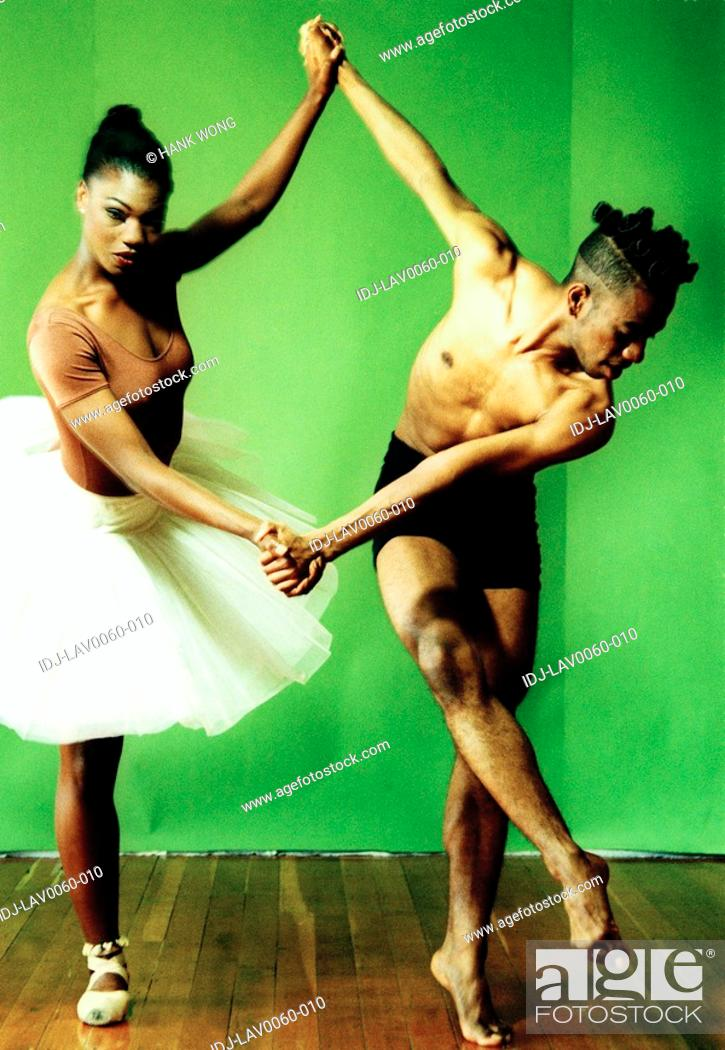 Stock Photo: Male and female ballet dancers holding hands of each other and dancing.