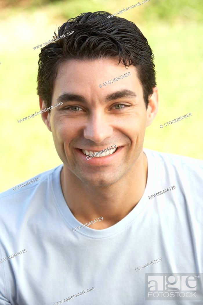 Stock Photo: Portrait Of Young Man Sitting In Park.