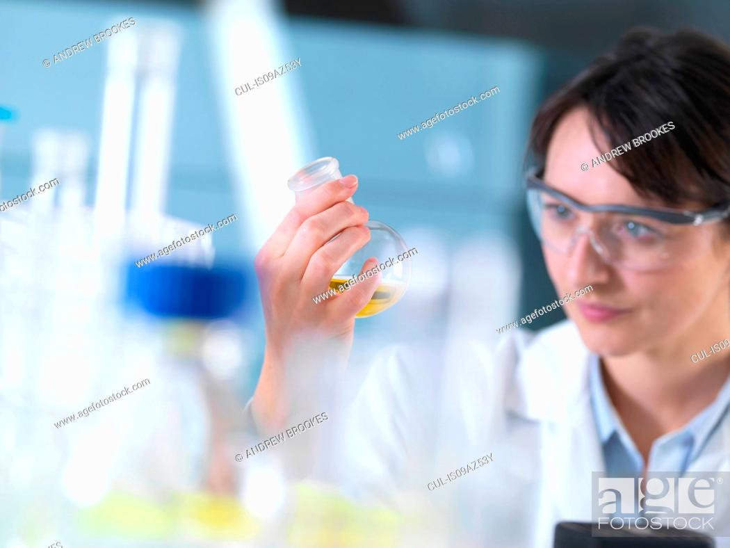 Stock Photo: Scientist viewing chemical formula in beaker during experiment in laboratory.