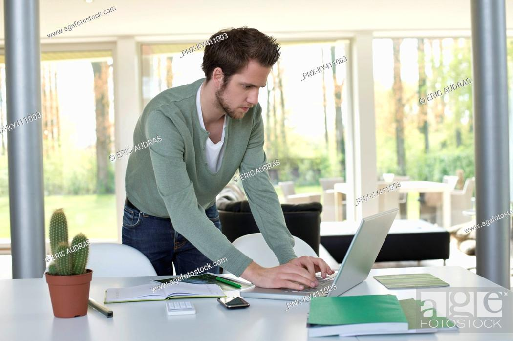 Stock Photo: Man working on a laptop with a cactus plant on the table.