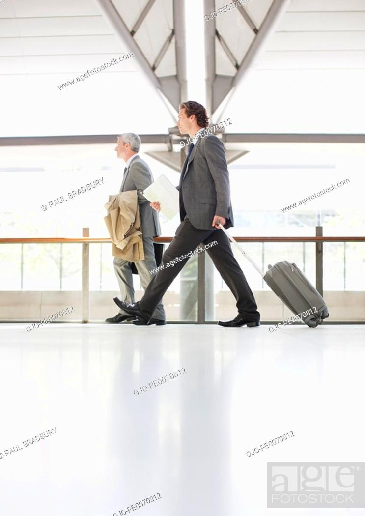 Stock Photo: Businessman pulling suitcase in train station.