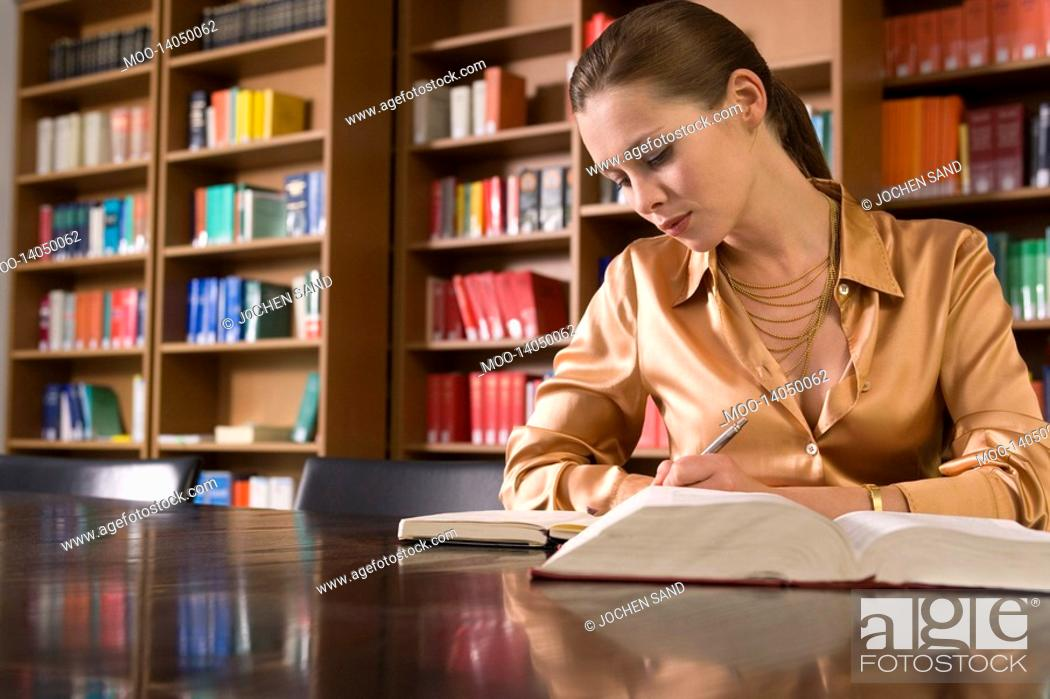 Stock Photo: Young woman writing at desk in library.