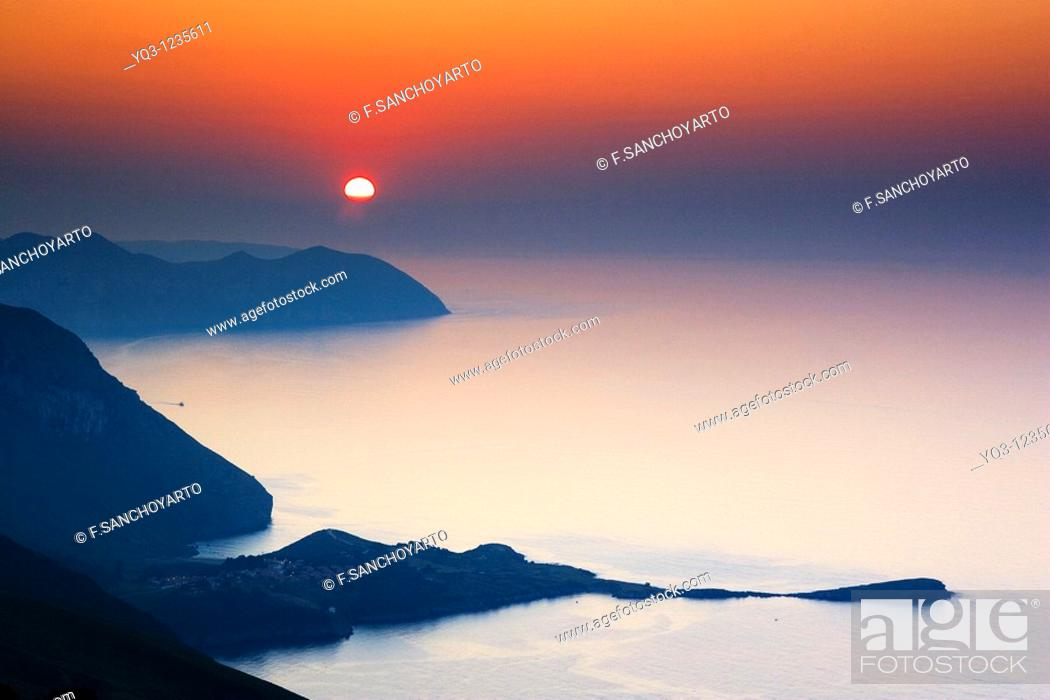 Stock Photo: Sun setting beyond La Ballena de Sonabia and El Buciero in Satoña, view from the top of Monte Cerredo, Castro Urdiales, Cantabria, Spain.