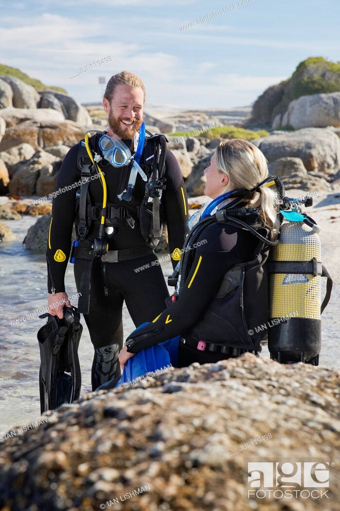 Stock Photo: Couple in wetsuits going ocean scuba diving from rocky beach.