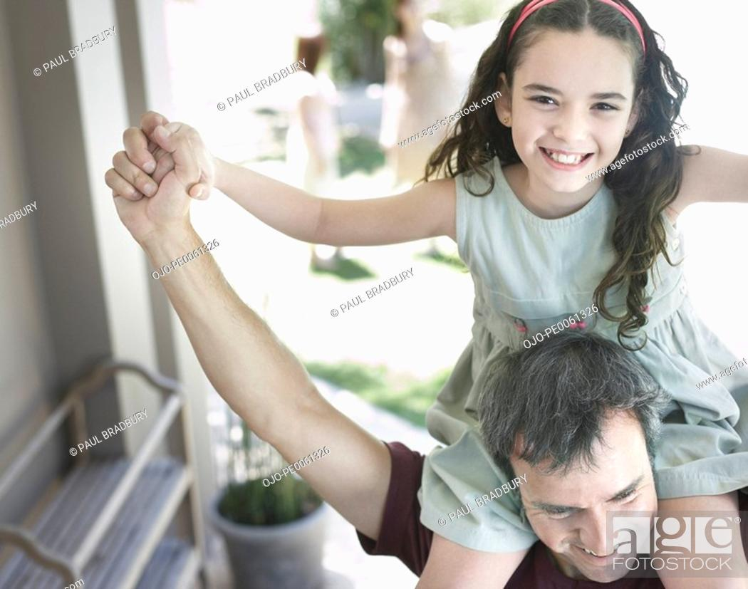 Stock Photo: Man outdoors giving young girl shoulder ride.