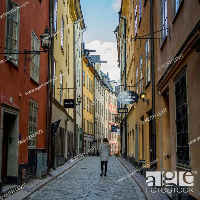 Imagen: A Woman Walking Down A Street Between Colourful Retail And Residential Buildings; Stockholm, Sweden.