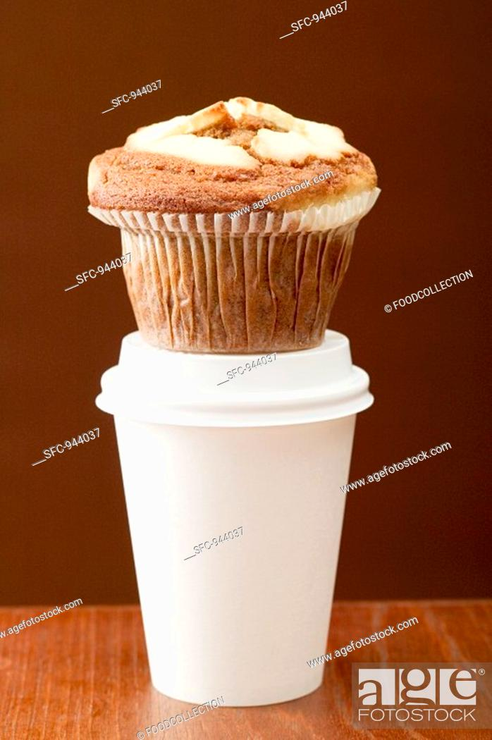 Stock Photo: A muffin on a plastic coffee cup.