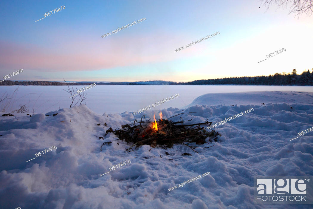 Stock Photo: Fire burning in the snow at the shore of a lake at sunset.