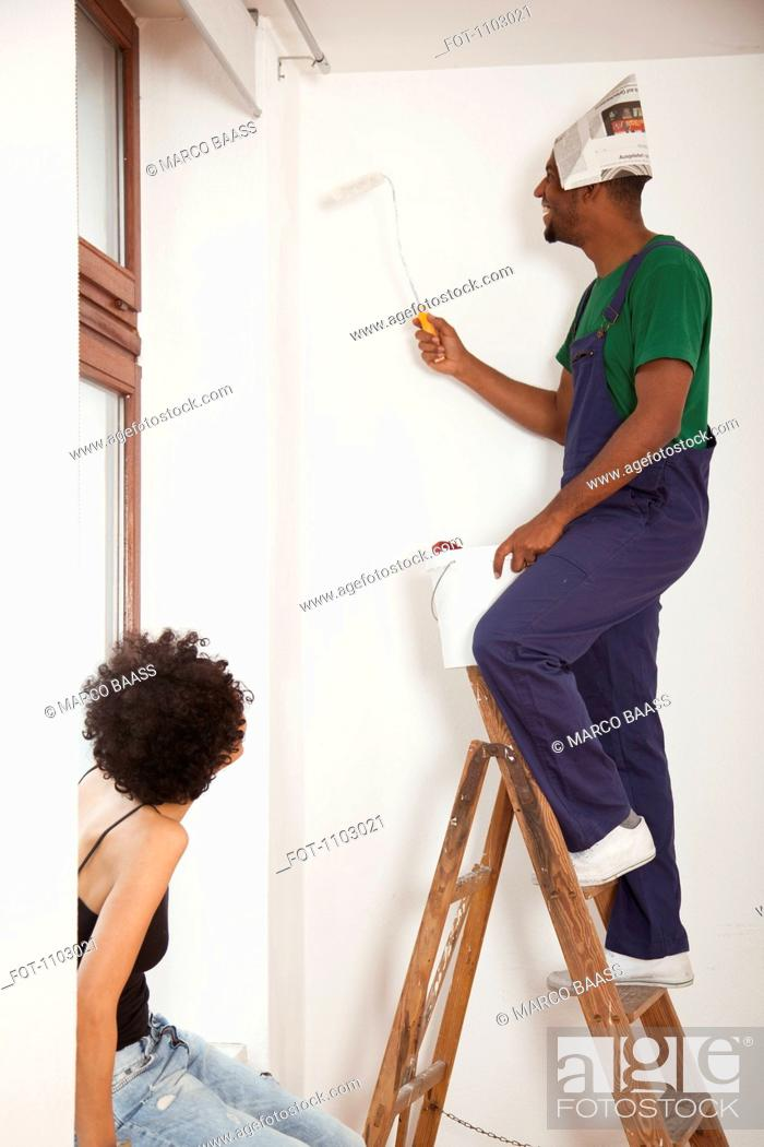 Stock Photo: A man standing on a ladder using a paint roller while a woman watches.