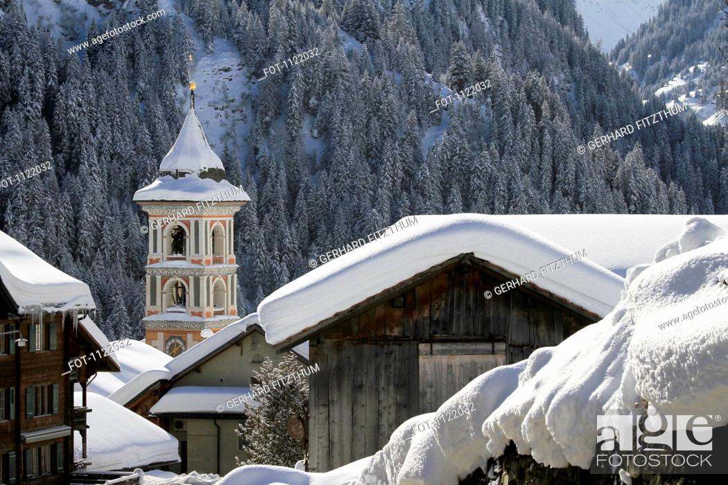 Stock Photo: Snow-capped village with mountain forest in the background.
