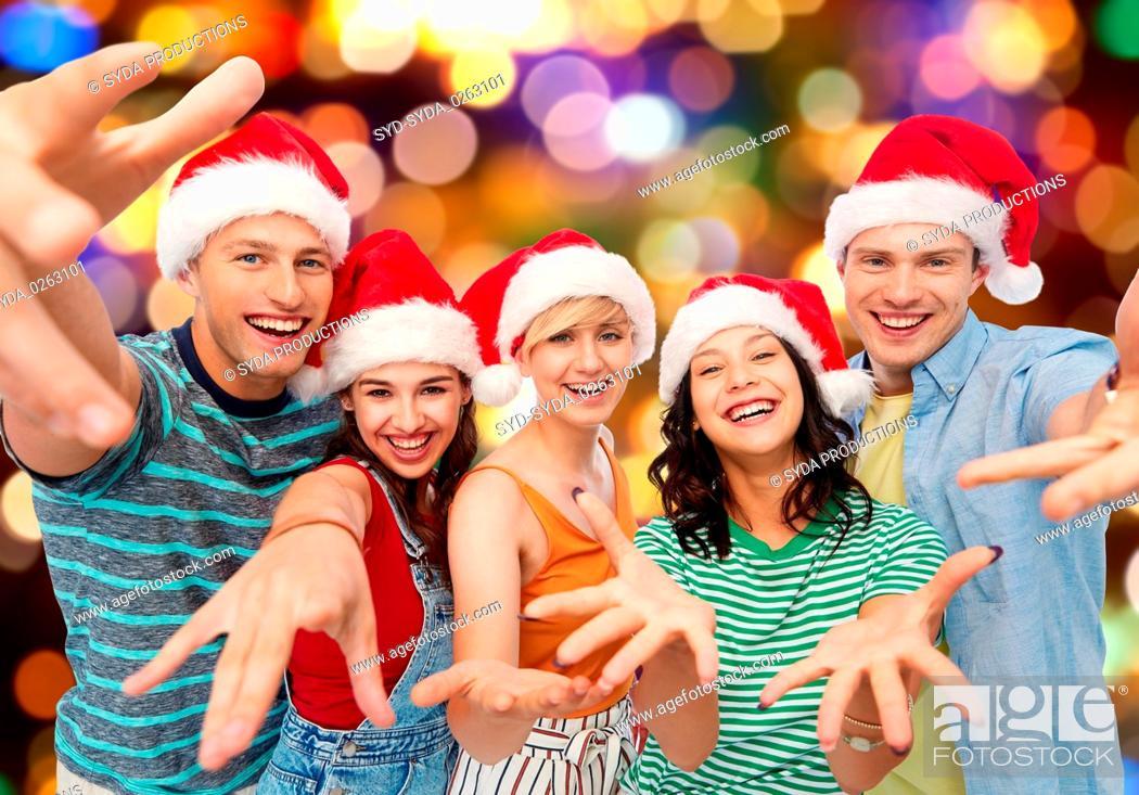 Stock Photo: happy friends in santa hats over festive lights.