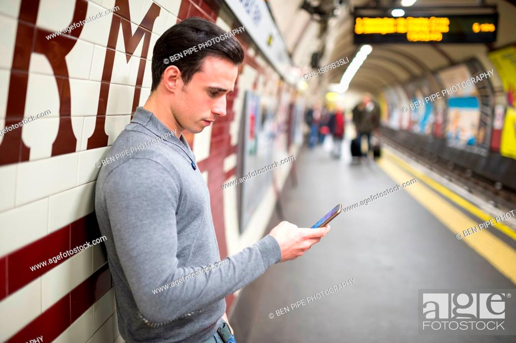 Stock Photo: Side view of man on railway platform looking at smartphone.