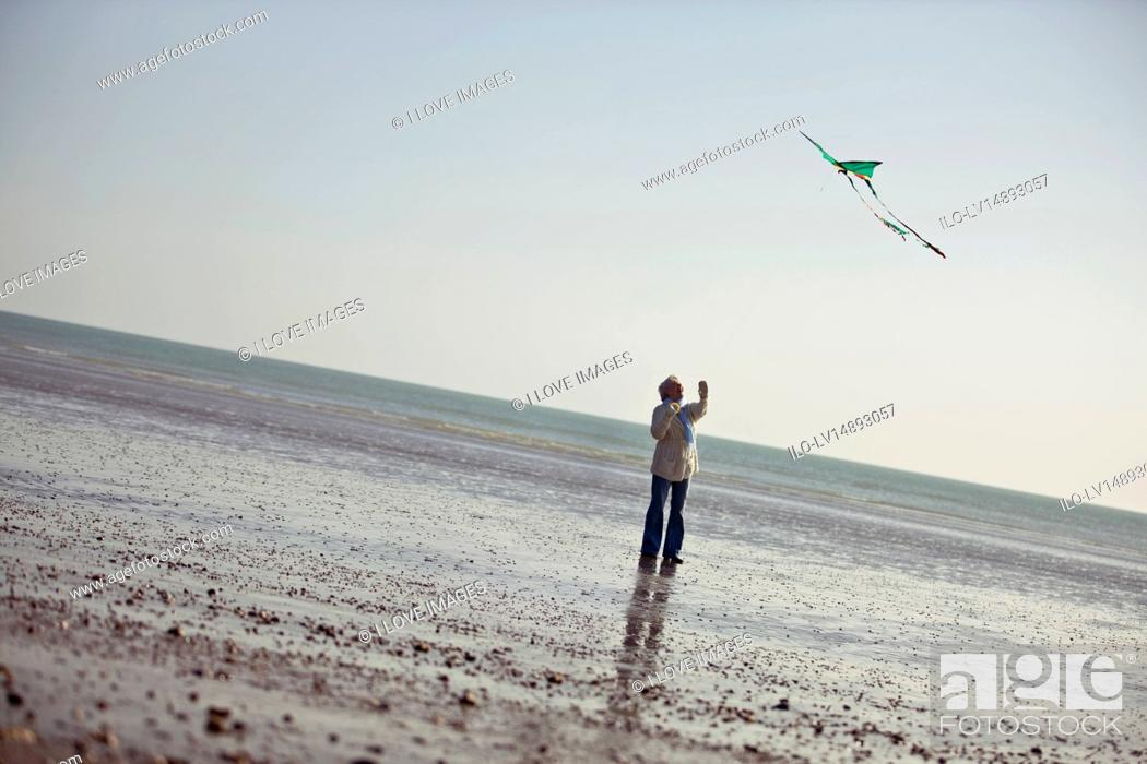 Stock Photo: A senior woman flying a kite on the beach.