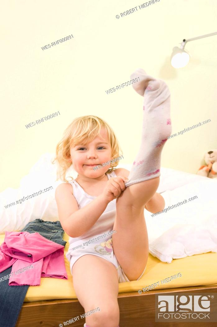 Stock Photo: Girl getting dressed on bed, putting on socks.