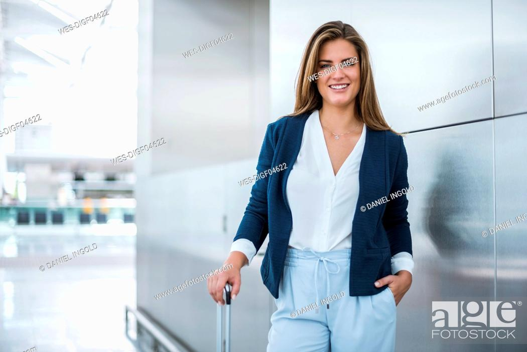 Stock Photo: Portrait of smiling young businesswoman with luggage.