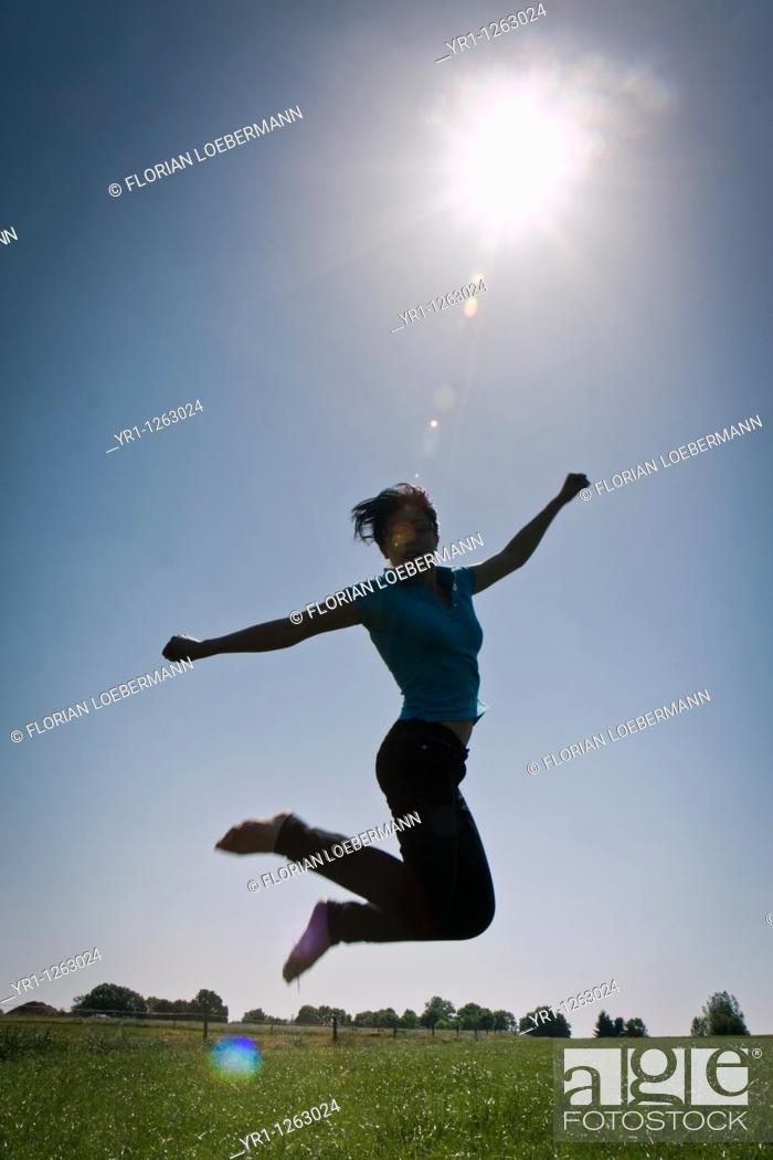 Stock Photo: Asian girl jumping in a field during summer. Shot in Aachen, Germany.