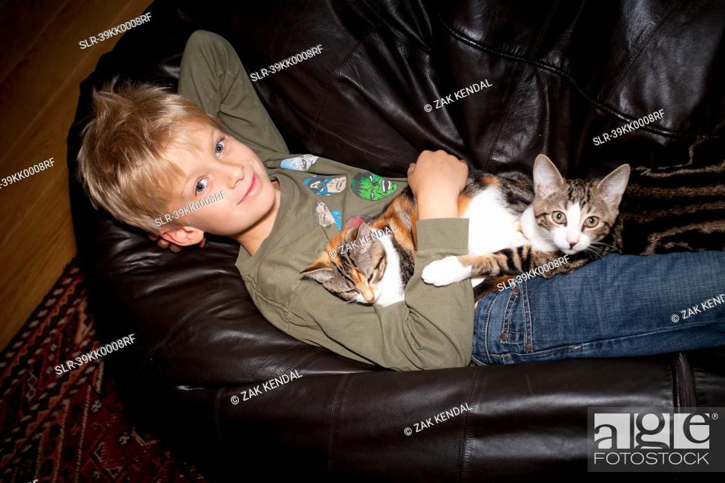 Stock Photo: Boy relaxing with cat on couch.