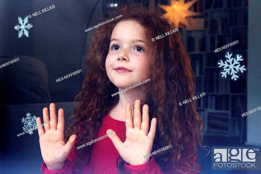 Imagen: Little girl standing at the window, waiting for Christmas.