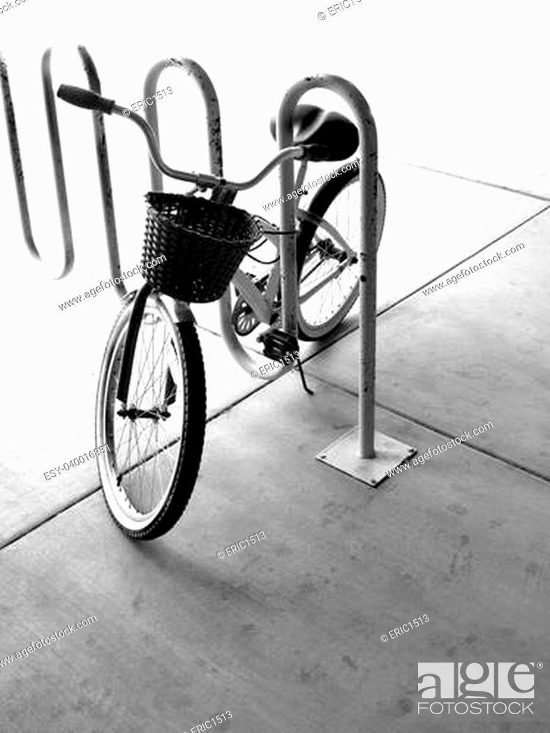 Stock Photo: A single bike with basket in a bike rack in a city.