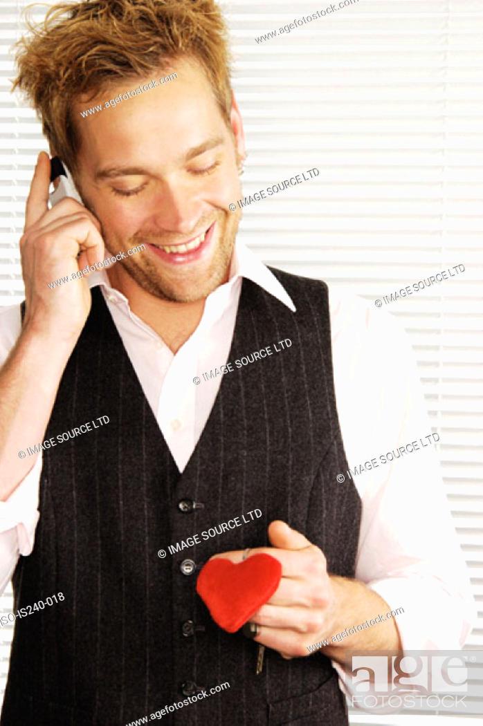 Stock Photo: Smiling man holding heart shaped keyring.