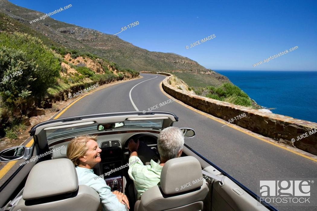 Stock Photo: Couple driving convertible on coast highway.