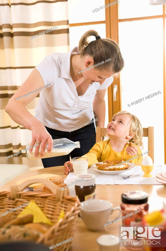 Stock Photo: Mother pouring milk for daughter breakfast, smiling.