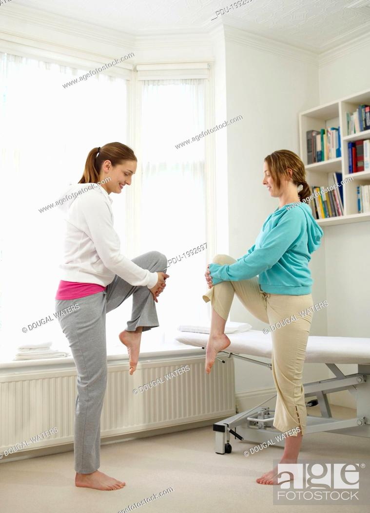 Stock Photo: Sports therapist demonstrating stretches.
