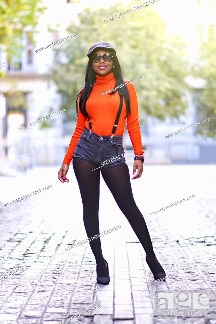 Stock Photo: Beautiful brown leather woman, model posing in the street dressed in modern clothes and high heel shoes.