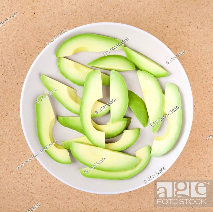 Stock Photo: Fresh sliced avocado on plate, over wooden background.