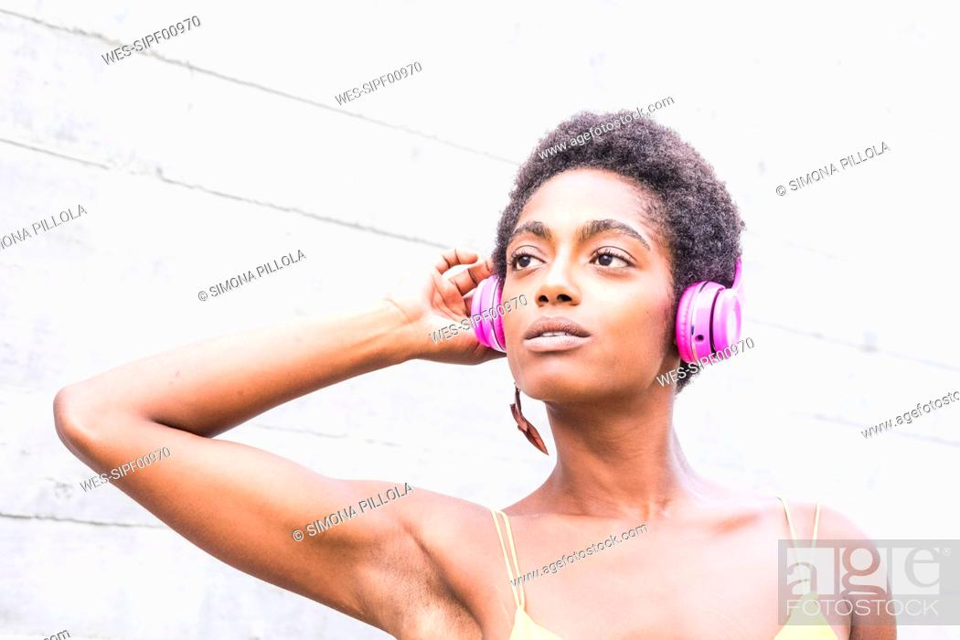 Stock Photo: Portrait of woman listening music with pink headphones.